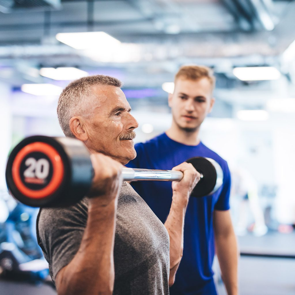 exercise physiologist assisting mature age man with strength training